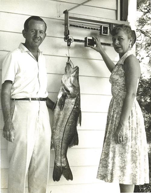 Frances Doucet weighing Jerry Pennock's big snook on the Fishing Club's front porch scale
