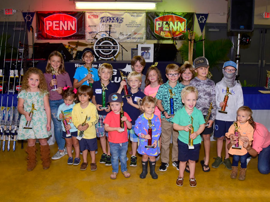 group of kids with fishing trophies